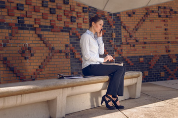 Eine Geschäftsfrau liest eine Zeitung und telefoniert