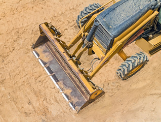 Yellow construction loader vehicle parked in sandy soil