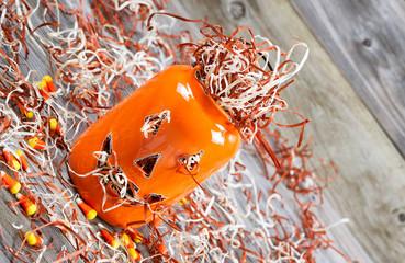 Angled scary orange pumpkin jar on rustic wood