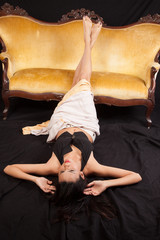woman laying down before a gold couch