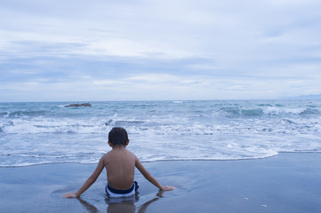 Boy sitting alone on the beach