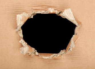 Hole in a corrugated cardboard with black background