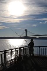 Fisherman is fishing near Varrazano-Narrows Bridge