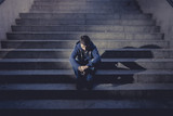 Young man lost in depression sitting on street stairs
