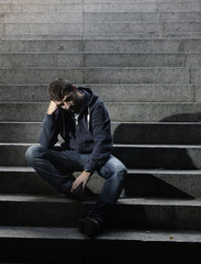Young sad man crying in depression sitting on street stairs
