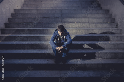 Young man lost in depression sitting on street stairs - 70234214