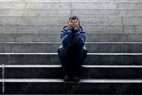 Young homeless man sad crying in depression on ground street