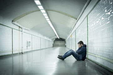 Young man lost in depression sitting on subway tunnel