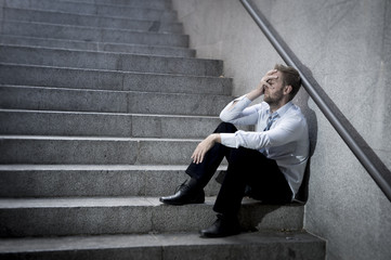businessman crying in depression sitting on street ground