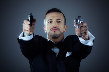 Sexy man in a tuxedo pointing two guns