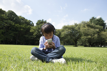 Boy listening to music with headphones in the park