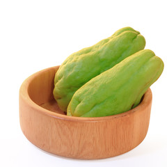 Chayote squash, also known as choko in wooden bowl on white