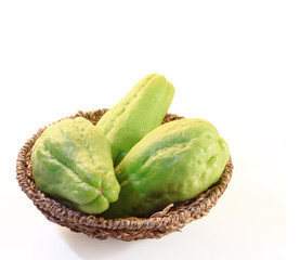 Chayote squash, also known as choko in basket on white