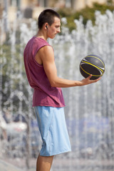 Guy looking at a basketball in his hand.