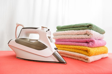 iron and laundry on the ironing board