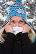 canvas print picture - Junge Frau im Winter beim Frieren mit Mütze im Wald