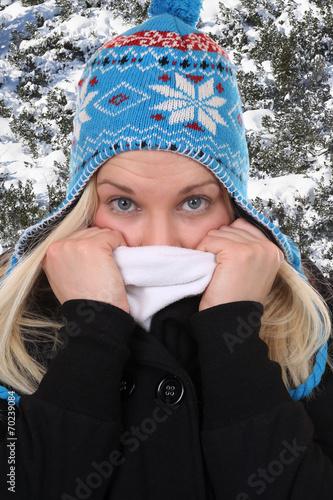 canvas print picture Junge Frau im Winter beim Frieren mit Mütze im Wald