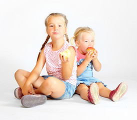 Two little girls eating fresh ripe apples.