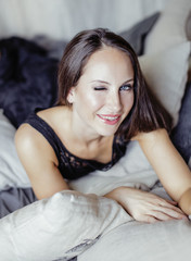 pretty young brunette woman in bedroom interior