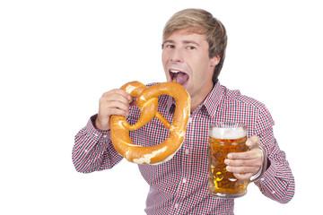 Mann in Tracht beißt in Bretzel und hält Bierkrug