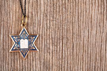 Star David pendant on wooden background