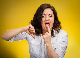 Woman showing Disgust thumbs down gesture yellow background