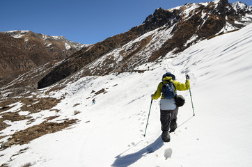 A lonely trekker hiking through snow high in mountains on a brig