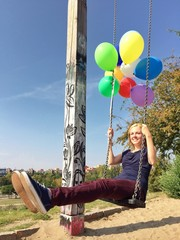 Mädchen schaukelt mit Luftballons
