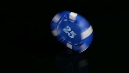 Poker Chips 25 turns on a black background. Slow motion