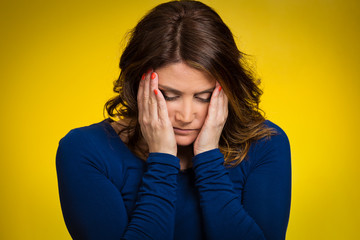 Headshot depressed, gloomy woman on yellow background