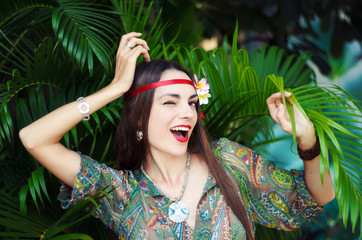 Hippie-girl with tropical flower in her long hair smiling and po