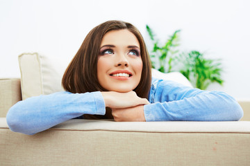 Smiling woman sitting on sofa.