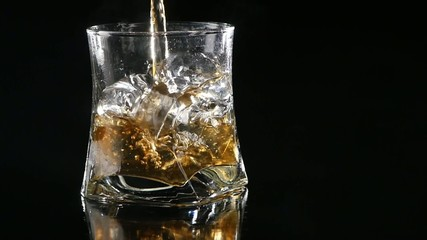 Whiskey being poured into a glass against black background.