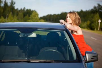 Молодая девушка возле автомобиля  на дороге летним днем