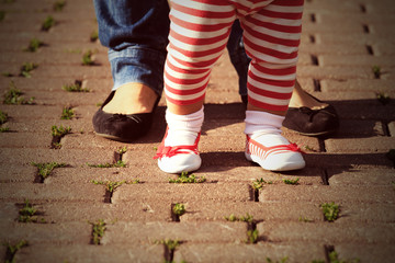 mother helping daughter to make first steps
