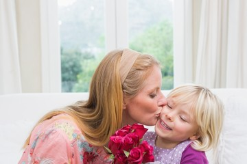 Happy woman holding red roses with daughter