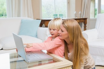 Cute daughter and mother using laptop on coffee table