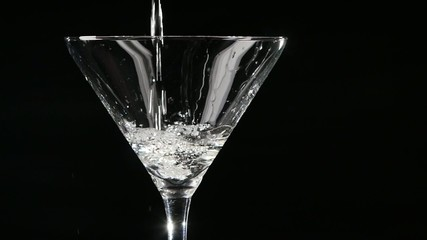 Martini being poured into a glass on black background. Slow