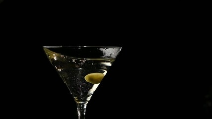 One olive falls into martini glass. Slow motion