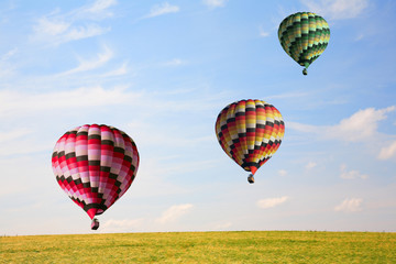 Three big balloons in the sky over a field