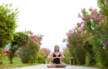 Красивая стройная девушка медитирует на природе летним днем