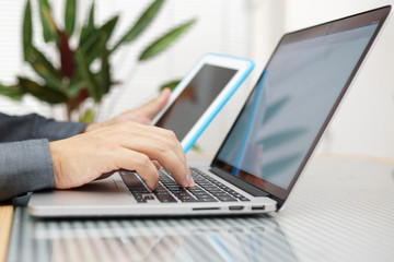 Man using laptop and tablet pc at the same time