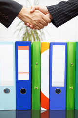 woman and man are handshaking over binders, handing business con