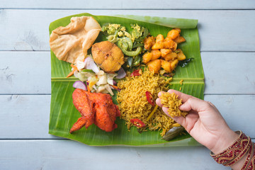 Indian woman eating biryani banana leaf rice