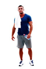 Handsome sportsman standing with towel and bottle with water
