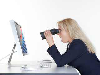 Shocked woman searching with spyglass on the internet