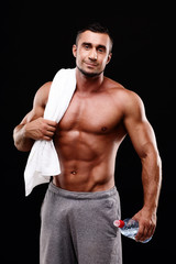 Handsome muscular sportsman holding towel and bottle with water