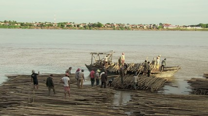 Workers loading bamboo canes on the small boat