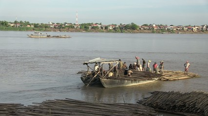 Boat loaded with bamboo canes leaving from bamboo rafts (2)