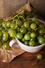 Green grapes in bowl on wooden background